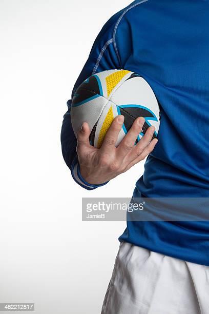 Gros plan d'un homme tenant un ballon de Rugby