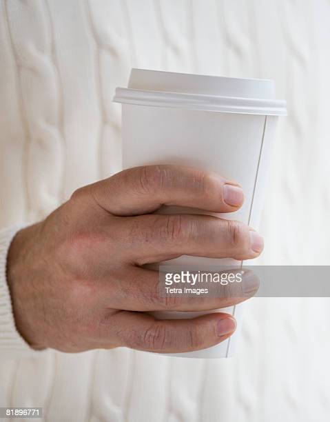 Close up of man holding take out coffee