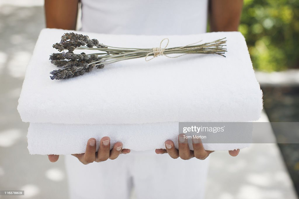 Close up of man holding towels with lavender : Stock Photo