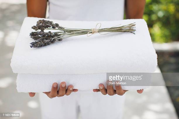 close up of man holding towels with lavender - health spa stock pictures, royalty-free photos & images
