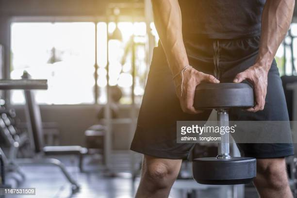 close up of man holding weight in gym - dumbbell stock pictures, royalty-free photos & images
