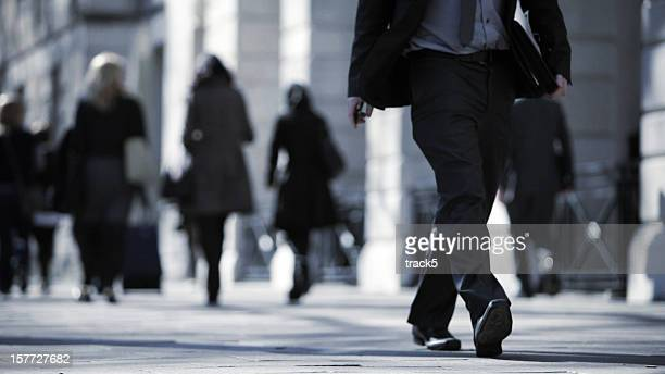 Close up of man in suit walking along busy street