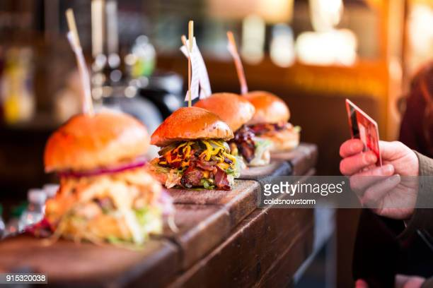 close up of man paying for fresh flame grilled burgers displayed in a row at food market using credit or debit card - street food stock pictures, royalty-free photos & images