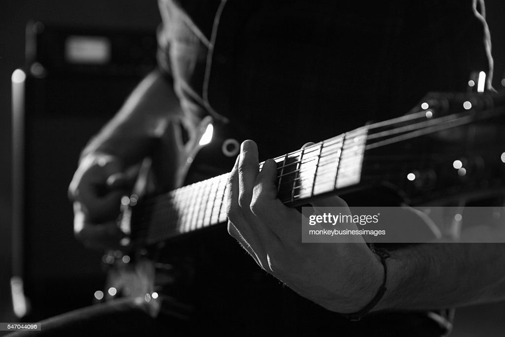 Black and white photo of man playing guitar musicians on stage close up of man playing electric guitar shot in monochrome