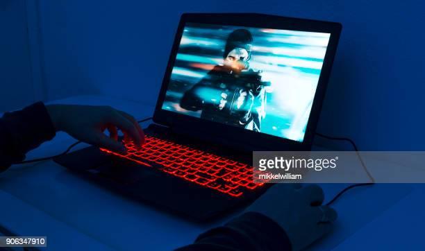 Close up of man playing on gaming laptop at night
