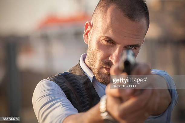 Close up of man poised with handgun looking at camera