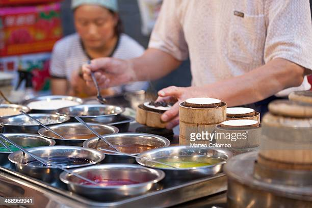 CONTENT] Close up of man preparing rice cakes at the street food night market in the muslim quarter of Xian Shaanxi China