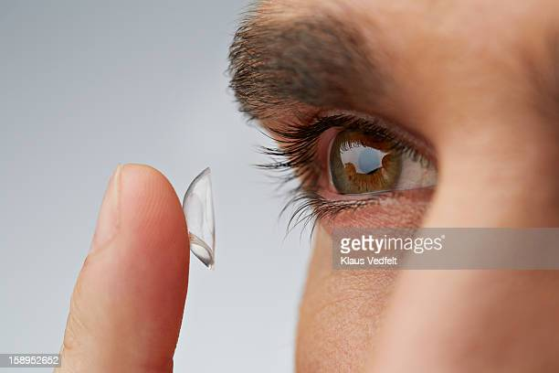 close up of man putting in contact lens - contacts stock photos and pictures