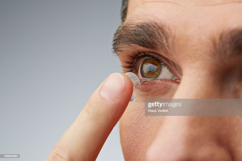 Close up of man putting in contact lens : Stock Photo