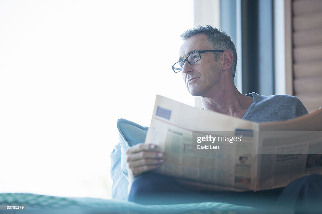 Close up of man reading newspaper in living room : Stock Photo