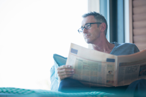 Close up of man reading newspaper in living room - gettyimageskorea