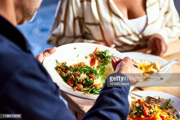 close up of man serving healthy food at dinner table - vegetarian food stock pictures, royalty-free photos & images