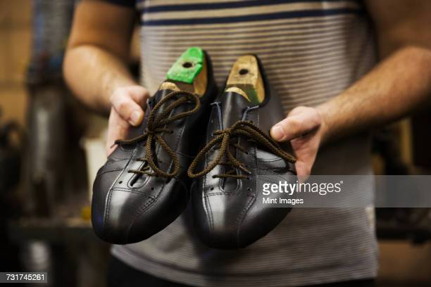 Close up of man standing in a shoemakers workshop, holding a pair of handmade cycling shoes.