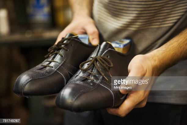 Close up of man standing in a shoemakers workshop, holding a pair of handmade leather lace up cycling shoes.