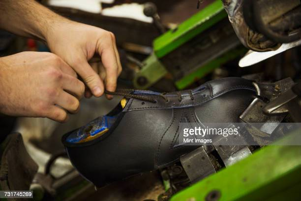 Close up of man standing in a shoemakers workshop, tying the laces of a leather cycling shoe.