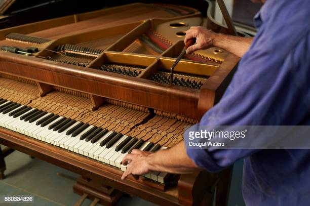Close up of man tuning traditional upright piano.