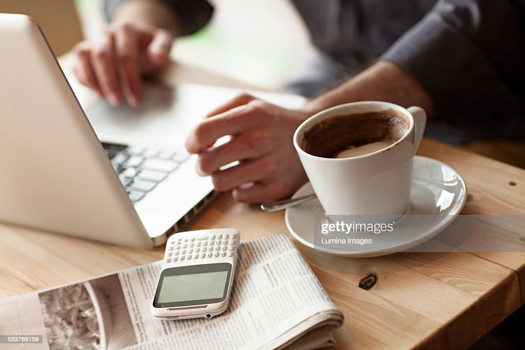 Close up of man using laptop with cup of coffee in cafe : Stock Photo