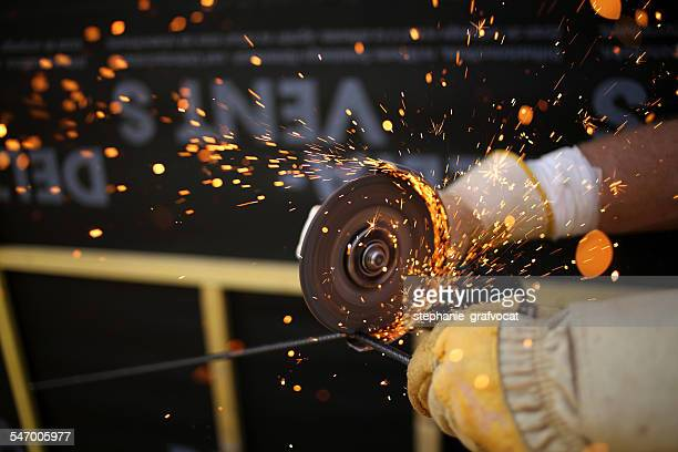 Close up of man using sanding tool on metal