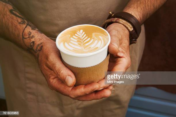 Close up of man with tattoo on his arm holding paper cup with cafe latte.