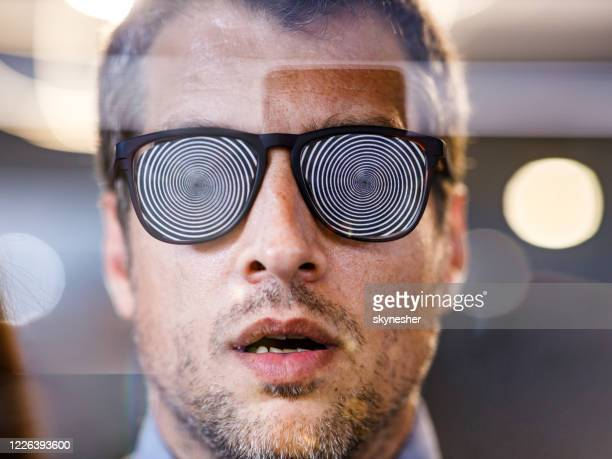 close up of manipulated man with hypnotic eyeglasses. - illusion stock pictures, royalty-free photos & images