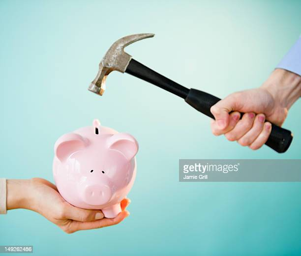 Close up of man's and woman's hands holding piggy bank and hammer, studio shot