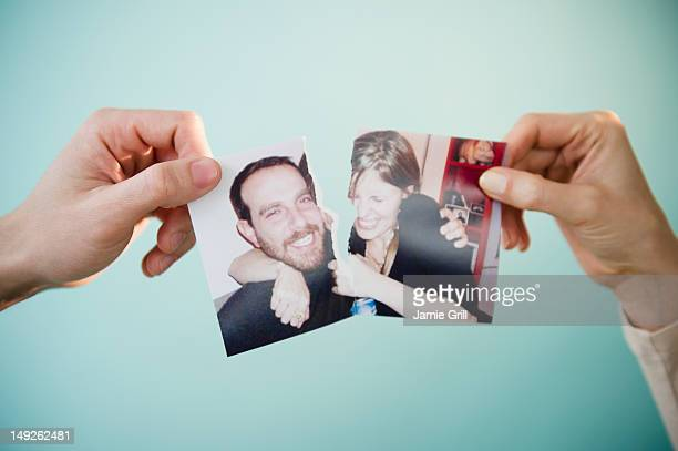 Close up of man's and woman's hands holding torn photograph of themselves, studio shot