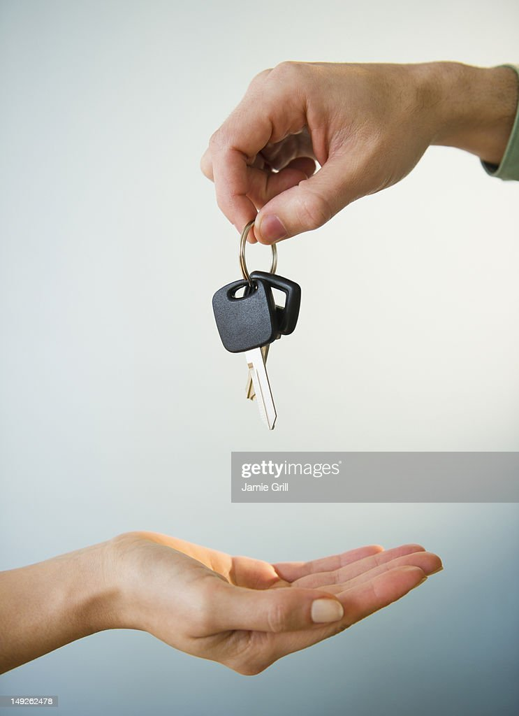 Close up of man's and woman's hands with car key, studio shot : Stock Photo