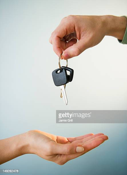 Close up of man's and woman's hands with car key, studio shot