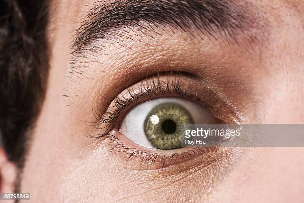 close up of man's eye looking surprised - staring stock photos and pictures