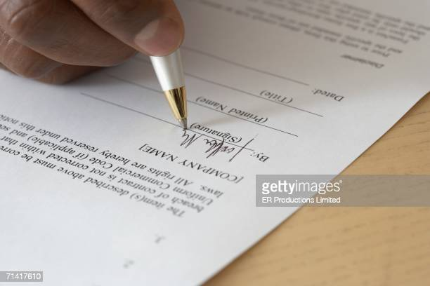 Close up of man's hand filling out form