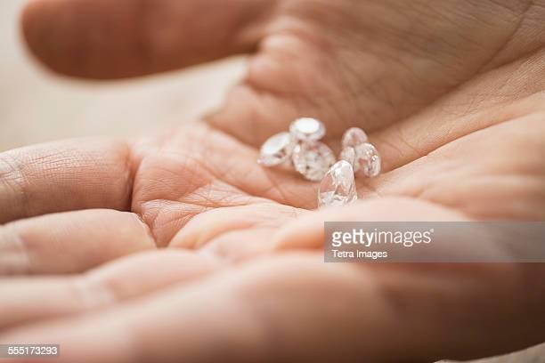 close up of mans hand holding diamonds - skin diamond photos et images de collection
