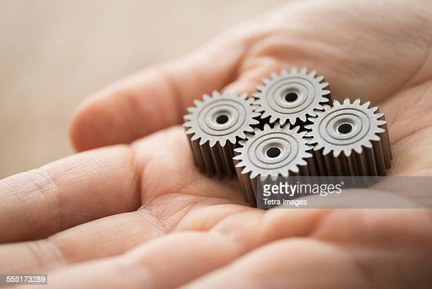 Close up of mans hand holding metal cogs