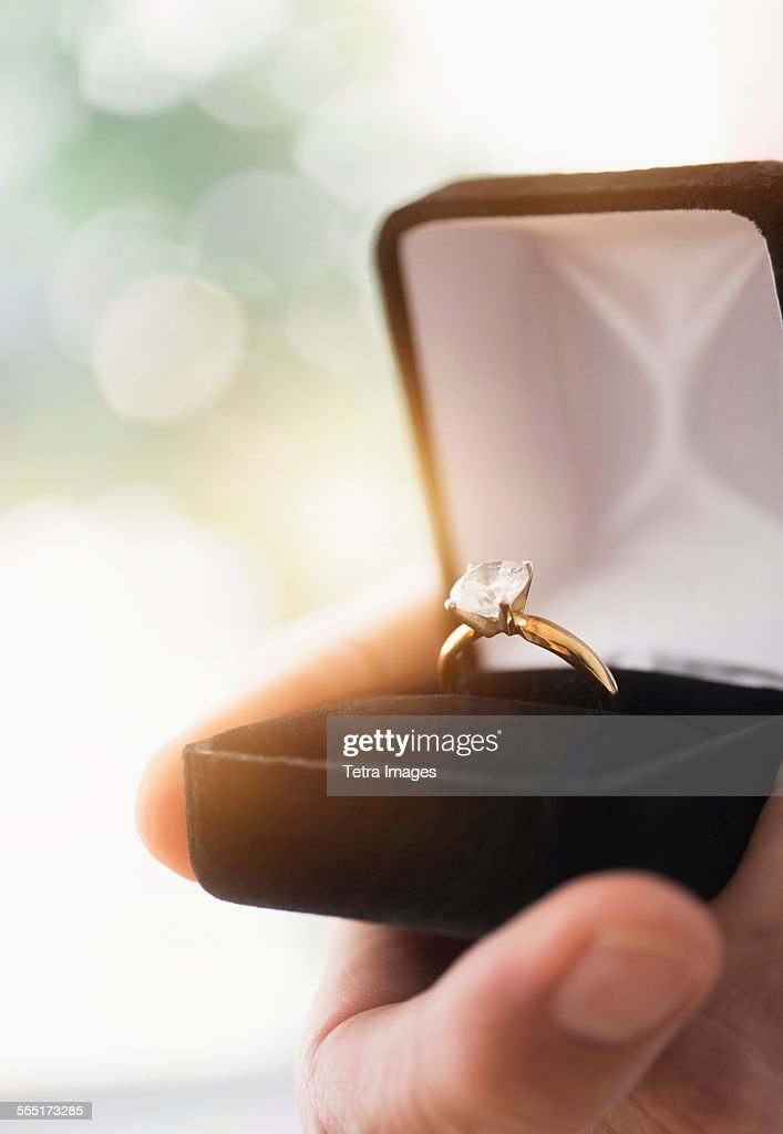 Close up of mans hand holding open box with engagement ring : Stock Photo
