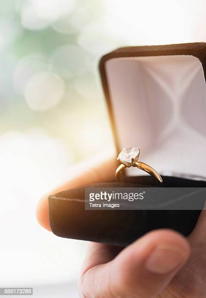 close up of mans hand holding open box with engagement ring - engagement ring box stock photos and pictures