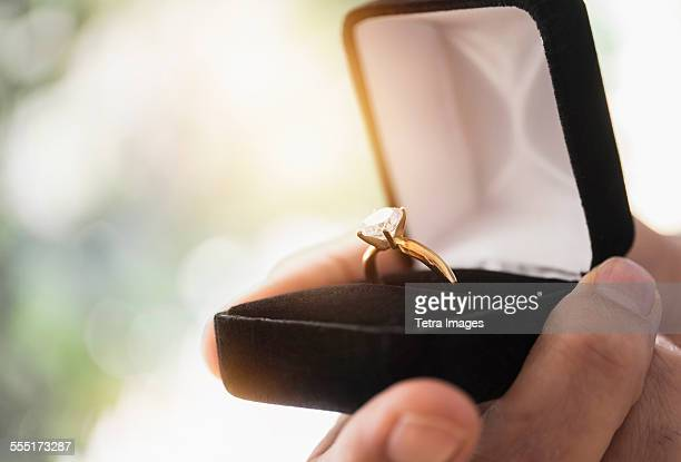 close up of mans hand holding open box with engagement ring - fidanzato foto e immagini stock