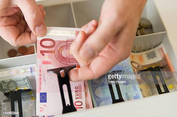 close up of man's hand putting banknotes into cash register, studio shot - banconote euro foto e immagini stock