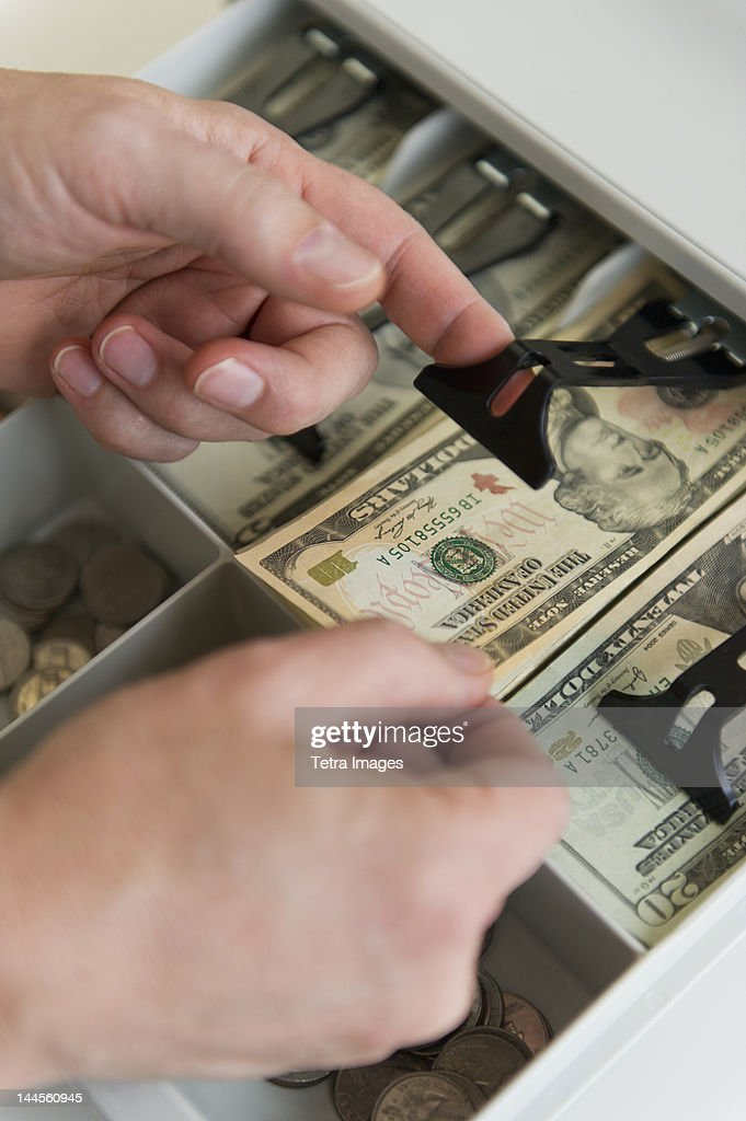 close up of mans hand putting banknotes into cash register studio