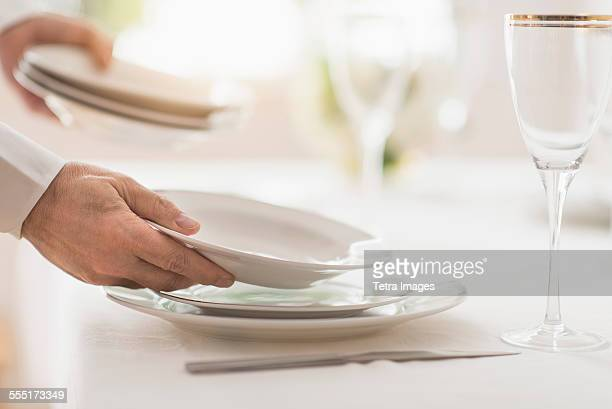 Close up of mans hand setting place in restaurant
