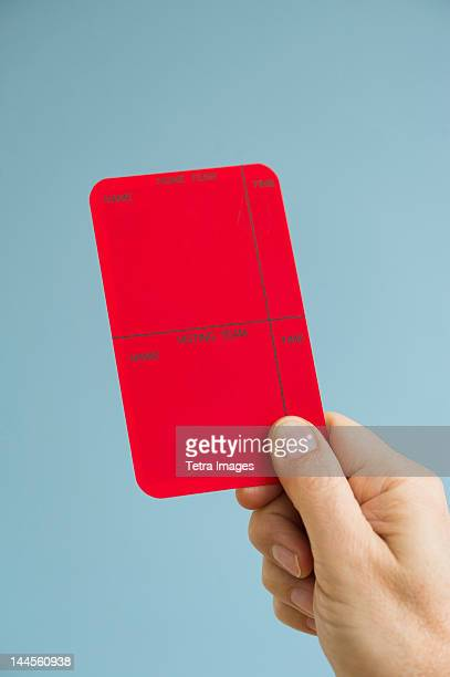 Close up of man's hand showing  red card, studio shot