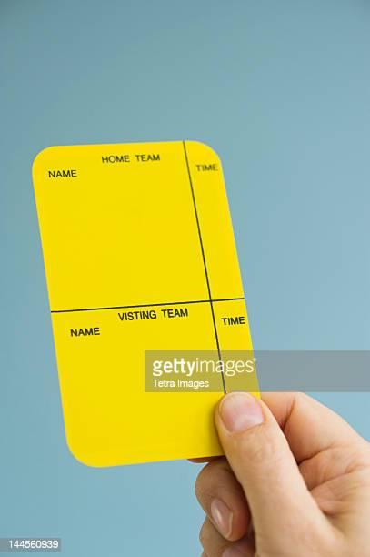 Close up of man's hand showing  yellow card, studio shot