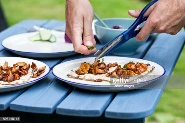 Close up of mans hands cutting herbs into dish