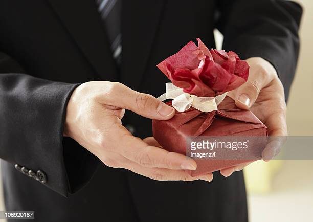 Close up of mans hands holding a gift