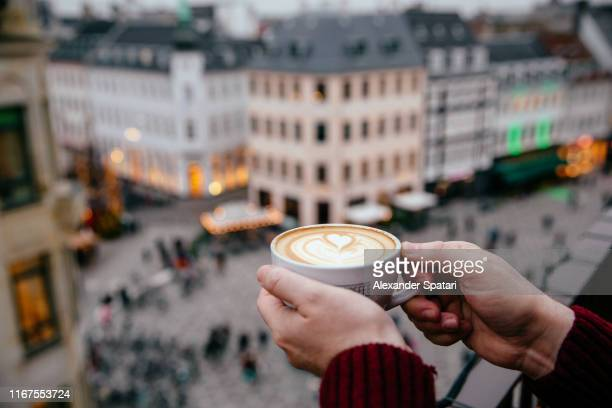 close up of man's hands holding cup of coffee against city skyline background - copenhagen stock pictures, royalty-free photos & images