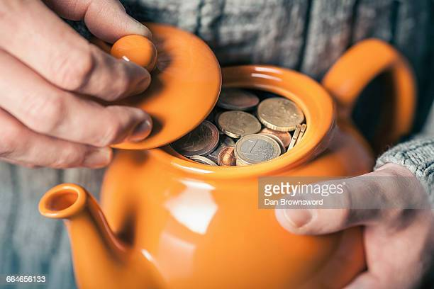 Close up of mans hands holding teapot full of coins