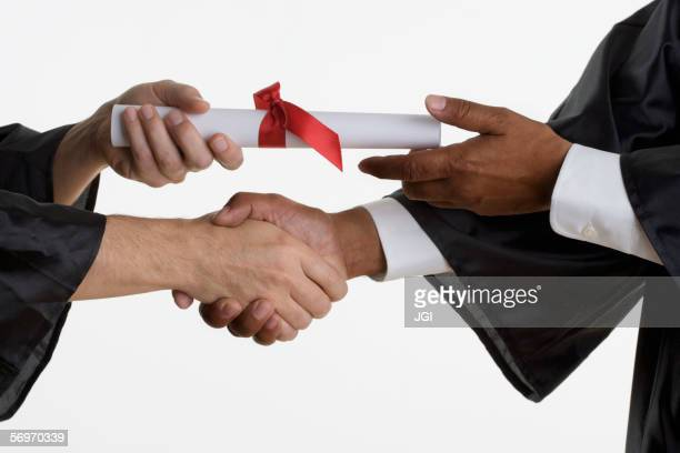 Close up of man's hands receiving diploma in graduation gown