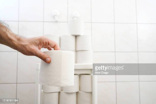 close up of man's with toilet paper. there are many of th storage in the background. - hemorroide fotografías e imágenes de stock