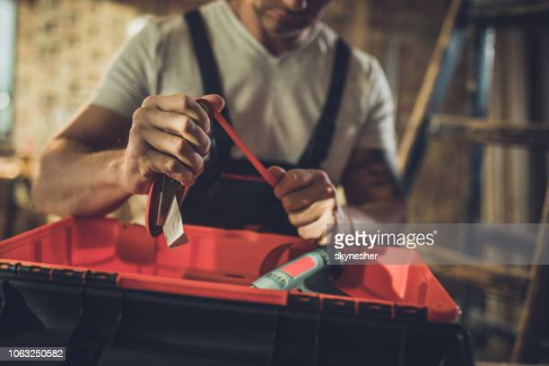 close up of manual worker packing his equipment into the toolbox. - toolbox stock pictures, royalty-free photos & images