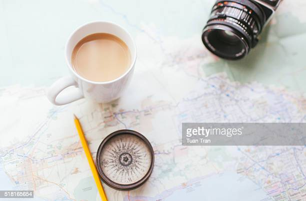 Close up of map, coffee cup, compass and camera