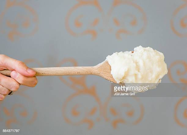 Close up of mashed potatoes on wooden spoon