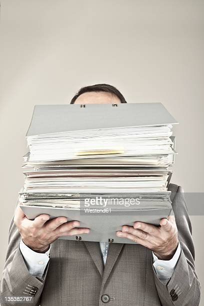 Close up of mature businessman at office holding stack of file